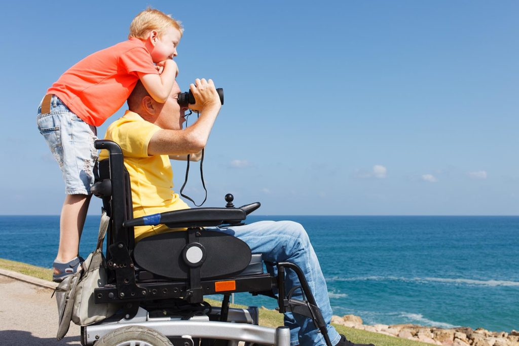 Father in motorized powerchair with son